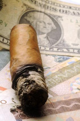 Zigarre auf US-Dollar und kubanischem Peso liegend